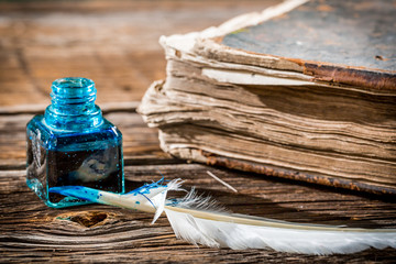 White feather on blue inkwell and old book