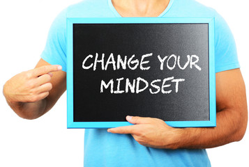 Man holding blackboard in hands and pointing the word CHANGE YOU