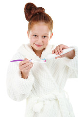 Beautiful little girl in bathrobe holding toothbrush and