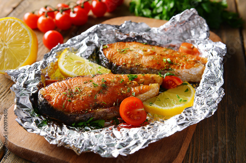 Tasty baked fish in foil on table close-up - 70970430
