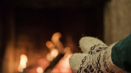 Woman relaxes by warm fireplace with a cup of tea