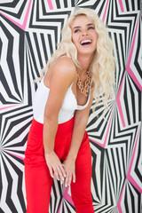 Seductive Young Blond Woman Posing at Printed Wall