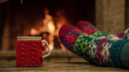 Woman relaxes by warm fire with a cup of hot drink