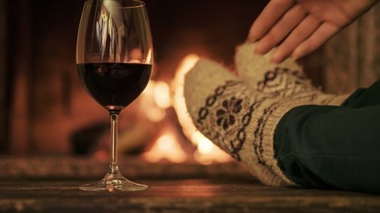Woman in woollen socks with a glass of wine by fireplace
