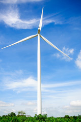 Wind turbine on the green meadow over the blue clouded sky
