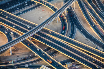 Highway roads with traffic in big city (Dubai) at sunset.