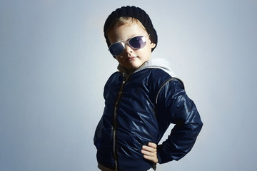 Fashion child in sunglasses.Posing Little boy.Blue background