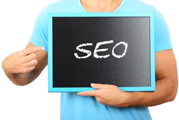 Man holding blackboard in hands and pointing the word SEO