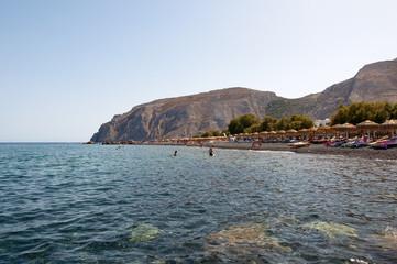 Tourists sunbathe on the Kamari Beach. Santorini,Greece.
