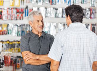 Man Conserving With Son In Hardware Store