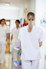 Technician Pushing Medical Cart In Hospital Hallway