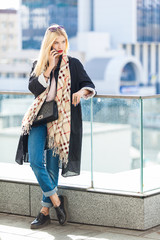 Stylish fashion portrait of blonde woman. Posing in the city