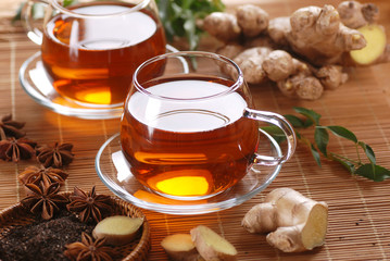 tè allo zenzero nella tazza di vetro con ingredienti intorno