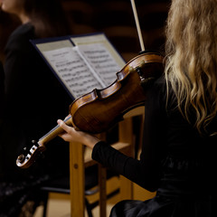 Violin in the hands of a girl in a symphony orchestra