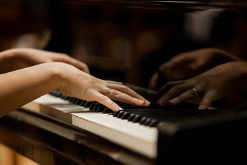 Woman's hands on the keyboard of the piano closeup