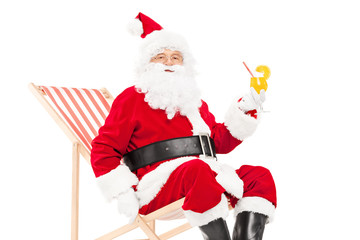 Santa Claus drinking a cocktail seated in sun lounger