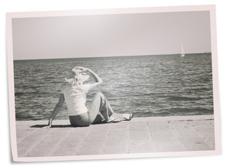 Faded holiday photo - woman on quay watches yacht. Retro filter.