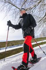 älterer Herr mit Schneeschuhen
