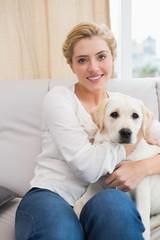 Happy blonde cuddling with puppy on sofa