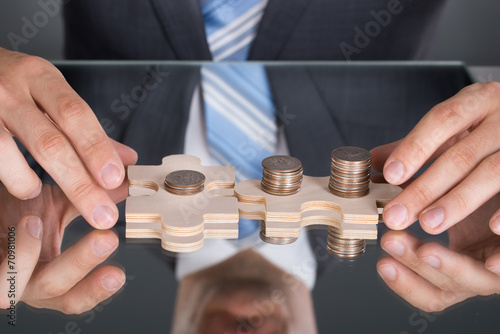 canvas print picture Hands connecting puzzle pices with coins