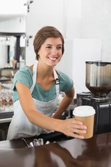 Pretty barista holding disposable cup