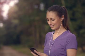 Attraktive junge Frau hört Musik mit ihrem Smartphone