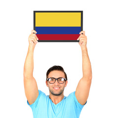 Portrait of a young casual man holding up board with National fl