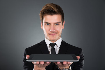 Portrait Of Confident Businessman Holding Digital Tablet