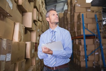 Manager holding clipboard in warehouse