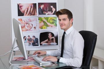 Photo Editor Using Laptop At Desk