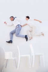 Business people jumping over chairs