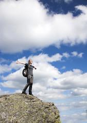 Woman on a cliff enjoying nature after a trek