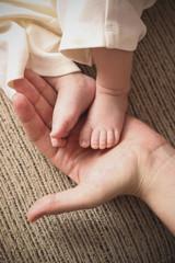 legs of a newborn baby in mother's hands