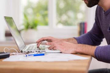 mann tippt zuhause auf dem laptop