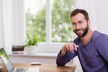 moderner typ arbietet zuhause am laptop