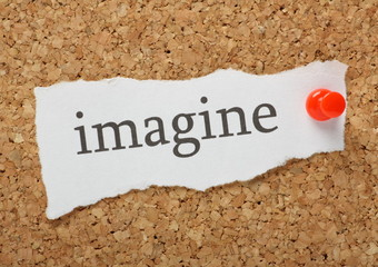 The word imagine on a cork notice board