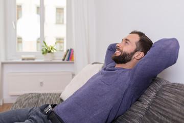 zufriedener mann sitzt auf dem sofa