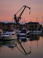 A dockside crane and boats, silhouetted against the setting sun
