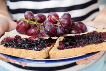 hand holding grape jelly sandwich