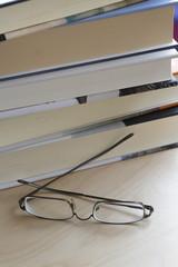 Libros amontonados y gafas