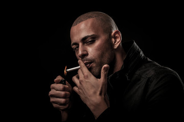 Handsome young man smokes cigarette in darkness - photography of