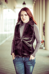 pretty redhead woman in waistcoat at city street