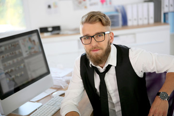 Young man with beard and eyeglasses in office