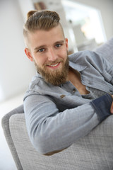Portrait of trendy guy with beard relaxing at home