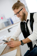 Treny guy in office sending text message with smartphone