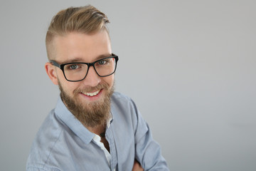Portrait of trendy smiling guy looking at camera, isolated