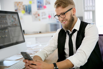 Trendy guy in office sending text message with smartphone