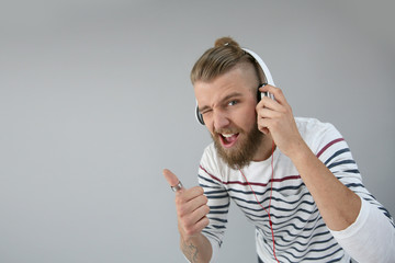 Trendy guy with headphones on showing thumb up