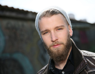Portrait of stylish guy with beard in street