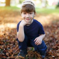 Little boy in cap posing in nature at autumn